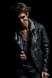 Young biker in leather jacket pulling his collar. And looks to the camera Royalty Free Stock Images