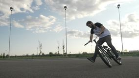 Young biker losing balance in mid air while landing on his bicycle and falling -. Young biker losing balance in mid air while landing on his bicycle and falling stock video footage