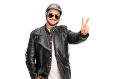 Young biker making a peace hand gesture Stock Photos