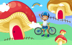 A young biker near the giant mushroom house Royalty Free Stock Photos