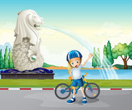 A young biker near the statue of Merlion Royalty Free Stock Photography
