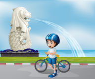 A young biker near the statue of Merlion Royalty Free Stock Images