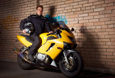 Young biker in night city. Young motorcyclist in a black coats sitting on the yellow sportbike and holding motorcycle helmet Royalty Free Stock Photo