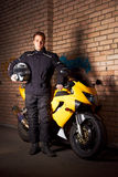 Young biker in night city. Young motorcyclist in a black coats standing at the yellow sportbike and holding motorcycle helmet Royalty Free Stock Photography