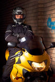 Young biker in night city. Young motorcyclist in a black coats and motorcycle helmet sitting on the yellow sportbike Royalty Free Stock Images