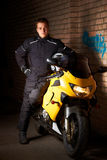 Young biker in night city. Young motorcyclist in a black coats standing at the yellow sportbike and holding motorcycle helmet Stock Photography