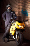 Young biker in night city. Young motorcyclist in a black coats and motorcycle helmet standing at the yellow sportbike Stock Images