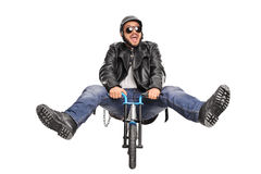 Young biker riding a very small bicycle and smiling Stock Photos