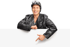 Young biker standing behind a billboard Stock Photography