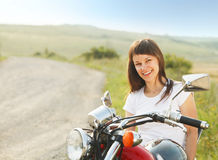 Young biker woman on the country road Royalty Free Stock Image