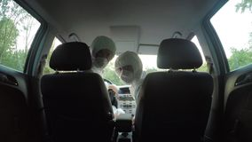 Young biohazard scientists technicians colleagues in hazmat suits in car turn looking at the backseat of the car - stock video footage