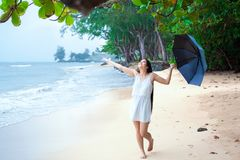 Woman in white dress on beach holding umbrella enjoying rain Stock Photos