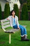 Young biracial teen girl relaxing outdoors on park bench Royalty Free Stock Photo