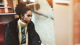 Young biracial woman in a metro car. Portrait of a charming young African-American female tourist on the seat of a subway train car; cute Brazilian girl is stock photography