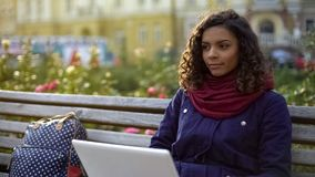 Young biracial writer working on new project, sitting with laptop outdoors. Stock footage Stock Photography