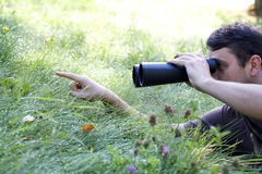 Young bird watcher holding binoculars. Young male bird watcher holding binoculars looking around royalty free stock image