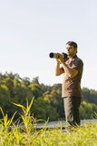 Young bird watcher with photo camera. Young male bird watcher standing holding photo camera with tele lenses stock images
