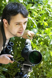Young bird watcher with telescope. Young male bird watcher holding telescope looking around stock image