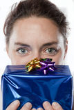 Young Birthday woman. Young woman holding up a birthday or Christmas gift to her face Royalty Free Stock Photo