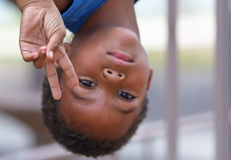 Young black African American boy. Portrait of young black African American boy hanging upside down with peace sign gesture Royalty Free Stock Photos