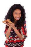 Young black african american teenage girl eating a slice of pizz Stock Photos