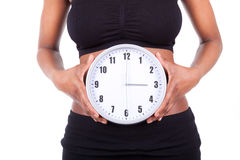 Young black african american woman holding a clock in front of h. Er belly, isolated on white background - African people Stock Photos