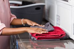 Young black African American woman washing her clothes in a automatic laundry royalty free stock photo