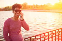Young black african man with cell phone over sunlight Royalty Free Stock Image