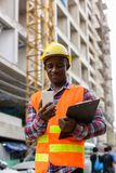 Young black African man construction worker holding clipboard wh. Ile using mobile phone at building site stock image