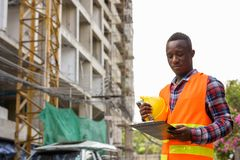 Young black African man construction worker reading on clipboard. While holding hard hat at building site stock photos