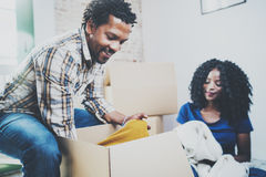 Young black american african couple with moving boxes in new apartment.Cheerful couple sitting in empty new house Stock Images