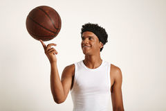Young black athlete balancing leather basketball on finger. Closeup shot of a playful smiling young attractive African American basketball player wearing a white Stock Photos