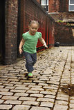Young black baby girl playing. On cobble stoned alley Royalty Free Stock Photos