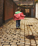 Young black baby girl playing. On cobble stoned alley Stock Photo