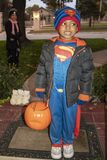 Young black boy dressed in superman costume with pumpkin candy basket and jacket standing at door trick r treating with mother loo stock photography