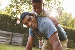 Young black boy playing on dad�s back in a garden, low angle Royalty Free Stock Image