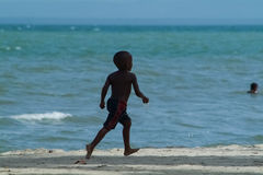A Young Black Boy Running on Beach. In front of the sea Royalty Free Stock Images