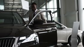 Young black businessman on auto salon background. Car sale and rent concept. Rich african american man stock video