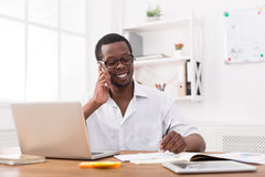 Young black businessman call mobile phone in modern white office Royalty Free Stock Images