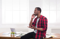 Young black businessman has a phone talk in modern white office Royalty Free Stock Photos