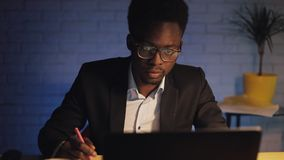 Young black businessman with laptop computer and papers working at night office. He signs the documents. Business stock footage