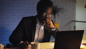 Young black businessman with laptop computer and papers working at night office. He signs the documents and drink coffee stock video footage