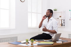 Young black businessman with mobile in modern white office Stock Image