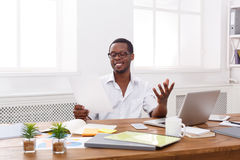 Young black businessman read documents in modern white office Royalty Free Stock Images