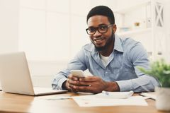 Young black businessman using mobile phone. Happy young black employee at workplace using mobile phone, checking social media on smartphone, taking break, copy Royalty Free Stock Images