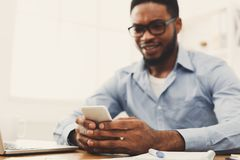 Young black businessman using mobile phone. Happy young black employee at workplace using mobile phone, checking social media on smartphone, taking break, copy Royalty Free Stock Photo
