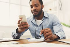 Young black businessman using mobile phone. Young black employee at workplace using mobile phone, checking social media on smartphone, taking break, copy space Royalty Free Stock Photos