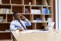 Young black businessman using smartphone in the boardroom royalty free stock image