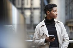 Young black businesswoman standing in the city with smartphone in hand, close up, selective focus royalty free stock photography