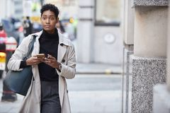 Young black businesswoman walking in the street in London using her smartphone, front view royalty free stock photography